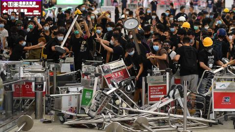 """Pro-democracy protestors block the entrance to the airport terminals after a scuffle with police at Hong Kong's international airport late on August 13, 2019. - Hundreds of flights were cancelled or suspended at Hong Kong's airport on August 13, 2019 as pro-democracy protesters staged a second disruptive sit-in at the sprawling complex, defying warnings from the city's leader who said they were heading down a """"path of no return"""". The new protest came as Beijing sent further ominous signals that the 10 weeks of unrest must end, with state-run media showing videos of security forces gathering across the border. (Photo by Manan VATSYAYANA / AFP)        (Photo credit should read MANAN VATSYAYANA/AFP/Getty Images)"""