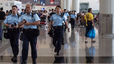 Police officers patrol in the departures hall of Hong Kong's International airport on August 14, 2019.