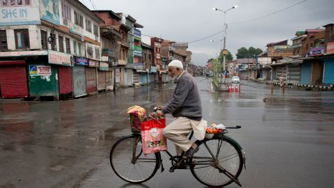 A Kashmiri man rides a bicycle through a deserted street during security lockdown in Srinagar, Indian-controlled Kashmir, on August 14, 2019.
