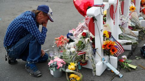 Antonio Basco cries beside a cross at a makeshift memorial near the scene of a mass shooting at a shopping complex, in El Paso, Texas.