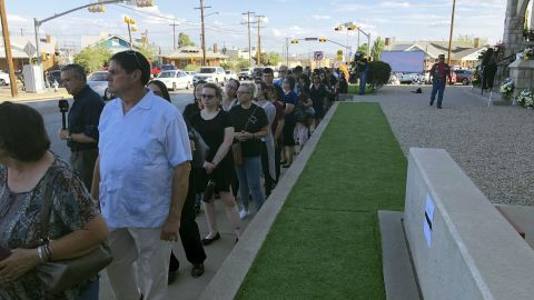 People wait in line in the heat to attend the memorial service for Reckard.