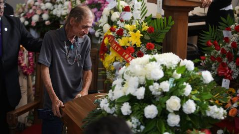 Basco leans on Reckard's casket during the funeral.