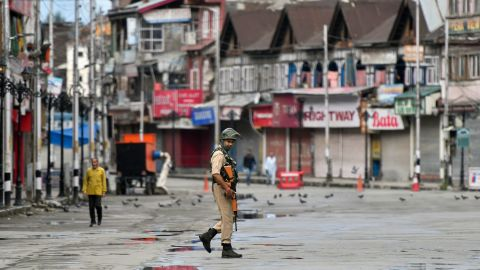 A security personnel patrols on a deserted road of the Lal Chowk area in Srinagar on August 19, 2019. - Some Kashmir schools re-opened on August 19 but many pupils stayed away, following weekend clashes after India stripped the region of its autonomy and imposed a lockdown two weeks ago. (Photo by PUNIT PARANJPE / AFP)        (Photo credit should read PUNIT PARANJPE/AFP/Getty Images)