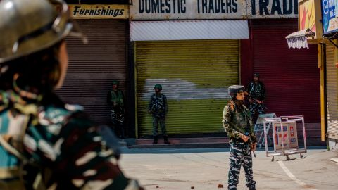 Indian paramilitary troopers stand guard in front the shuttered shops in the deserted city center, on August 20, 2019 in Srinagar.