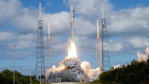 KENNEDY SPACE CENTER, FLA.  —   Into a cloud-scattered blue sky, NASA's New Horizons spacecraft roars off the launch pad aboard an Atlas V rocket spewing flames and smoke.  Liftoff was on time at 2 p.m. EST from Complex 41 on Cape Canaveral Air Force Station in Florida. This was the third launch attempt in as many days after scrubs due to weather concerns.   The compact, 1,050-pound piano-sized probe will get a boost from a kick-stage solid propellant motor for its journey to Pluto. New Horizons will be the fastest spacecraft ever launched, reaching lunar orbit distance in just nine hours and passing Jupiter 13 months later. The New Horizons science payload, developed under direction of Southwest Research Institute, includes imaging infrared and ultraviolet spectrometers, a multi-color camera, a long-range telescopic camera, two particle spectrometers, a space-dust detector and a radio science experiment. The dust counter was designed and built by students at the University of Colorado, Boulder. The launch at this time allows New Horizons to fly past Jupiter in early 2007 and use the planet's gravity as a slingshot toward Pluto. The Jupiter flyby trims the trip to Pluto by as many as five years and provides opportunities to test the spacecraft's instruments and flyby capabilities on the Jupiter system. New Horizons could reach the Pluto system as early as mid-2015, conducting a five-month-long study possible only from the close-up vantage of a spacecraft.