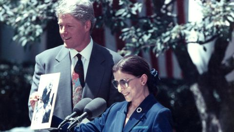 """President Bill Clinton nominated Ginsburg to the US Supreme Court in June 1993. Here, Ginsburg is holding a photograph of Hillary Clinton singing """"the toothbrush song"""" with Ginsburg's granddaughter Clara and her nursery school class."""
