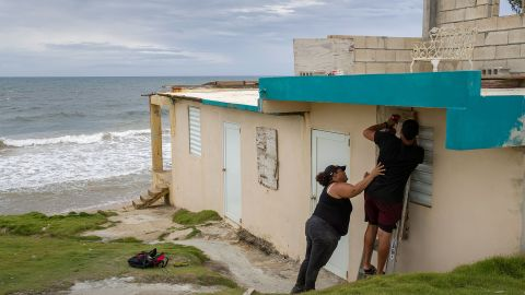 Ya Mary Morales and Henry Sustache put plywood over the windows of their home in Yabucoa, Puerto Rico, on August 28. Puerto Rico was ultimately spared the brunt of hurricane-force winds.