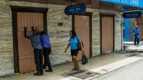 Residents board up a storefront pharmacy in Bridgetown, Barbados, on Monday, August 26.