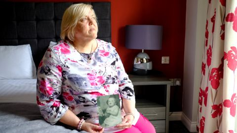 Survivor Teresa O'Sullivan holds a photo of herself as a baby, a photograph that was taken of children who were to be adopted from Tuam home.