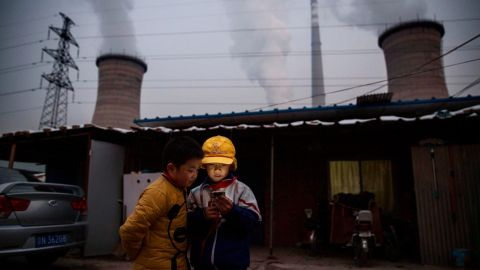 Chinese boys look at their smartphone in front of their house next to a coal fired power plant on the outskirts of Beijing, China.