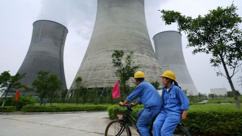 Workers cycle past power stations in Guangan, in southwest China's Sichuan province.