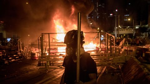 A protesters walks in front of a burning barricade after clashing with police at an anti-government rally on August 31, 2019 in Hong Kong.