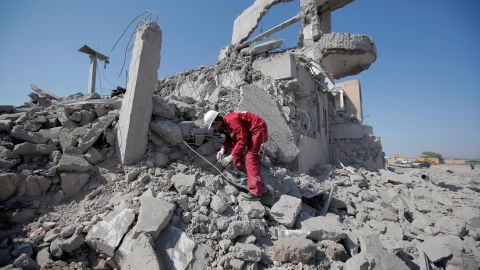 A rescue worker recovers a body from under the rubble of the detention center following the strikes.