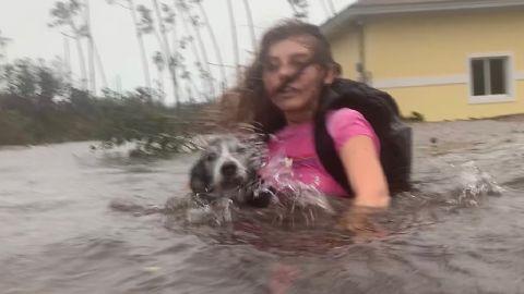 Julia Aylen carries her dog as she wades through waist-deep water near her home in Freeport on September 3.
