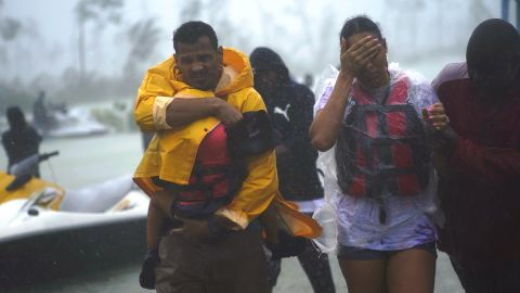 A family is escorted to a safe zone after being rescued in Freeport, Bahamas, on  September 3.