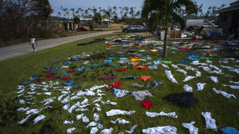 A child walks past clothes laid out to dry in Freeport, Bahamas, on September 4.