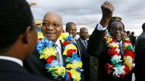South African President Jacob Zuma walks with Mugabe at Harare International Airport in March 2010.
