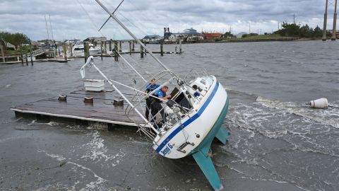 Police Officer Curtis Resor, left, and Sgt. Michael Stephens check a sailboat for occupants in Beaufort, North Carolina, on September 6.