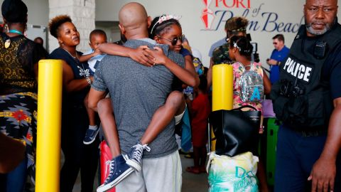 Mark Winder, center, of Tampa, Fla., embraces his niece, Gabriella Winder, 10, of Freeport, Grand Bahamas, as Gabriella and her family arrive to the Port of Palm Beach on the Grand Champion cruise ship in Riviera Beach, Fla., on Saturday, Sept. 7, 2019. The ship transported passengers leaving Freeport,  that were effected by the damaged caused by Hurricane Dorian. (AP Photo/Brynn Anderson)