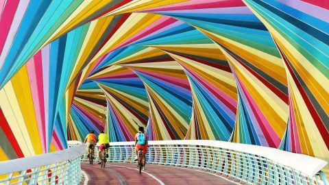 <strong>Qingdao, China: </strong>Cyclists pass through a gaily colored footbridge in east China's Shandong province.