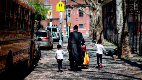 A Jewish man walks with his children down a street in Williamsburg, Brooklyn.