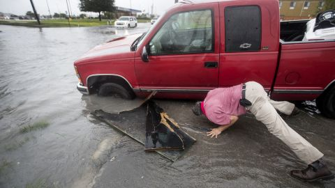 Felipe Morales works Tuesday on getting his truck out of a ditch filled with high water in Houston.