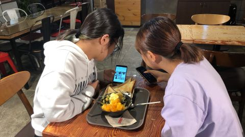 Yoo Chae-rin (left) shows photos of various hairstyles to her friend Kim Hyo-min  (right) in a coffee shop near Seoul in September 2019.