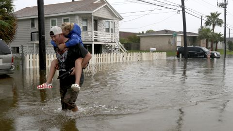 A father carries his daughter through high water in Galveston, Texas, after Imelda caused flooding in the area.