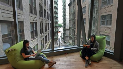BOSTON, MA - JULY 18: Employees sit with a window view of old Boston behind Congress Street at the new headquarters of Boston catering service ezCater at 40 Water St. on July 18, 2019. The space features one twist on the typical tech office setup: The whole place is actually a WeWork. The coworking giant leased the space from building owner Related Beal, then rented it to ezCater for the next five years, part of a growing push by WeWork into more traditional corporate office leasing. WeWork has similar arrangements in other cities but this is the first of its kind to open in Boston. Its planning more. (Photo by David L. Ryan/The Boston Globe via Getty Images)