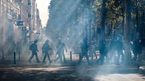 Police walk through a tear gas cloud on the Champs-Élysées Saturday.