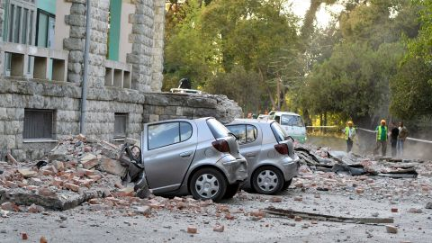 Vehicles are crushed as emergency services workers clear the ruins of a collapsed building roof in Tirana, Albania, after an earthquake.
