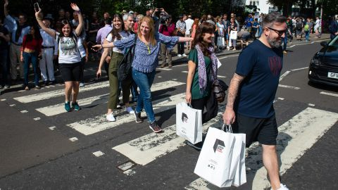 Beatles fans walk across the Abbey Road crossing in London on August 8 2019 to mark the 50th anniversary of the iconic cover album.