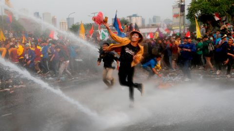 Student protesters hurl objects as they are sprayed by a police water cannon truck during a protest outside the parliament in Jakarta, Indonesia, on September 24, 2019.