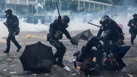 """Police detain demonstrators in the Sha Tin district of Hong Kong on October 1, 2019, as violent demonstrations take place in the streets of the city on the National Day holiday to mark the 70th anniversary of communist China's founding. - Strife-torn Hong Kong on October 1 marked the 70th anniversary of communist China's founding with defiant """"Day of Grief"""" protests and fresh clashes with police as pro-democracy activists ignored a ban and took to the streets across the city. (Photo by ISAAC LAWRENCE / AFP)        (Photo credit should read ISAAC LAWRENCE/AFP/Getty Images)"""