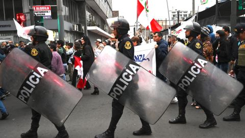 Police in LIma as demonstrators march on September 30.