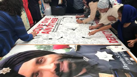 Mourners sign a banner dedicated to Dhaliwal on Wednesday, in a hall near the arena where the funeral is being held.