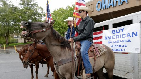 Cowboys carry the colors outside a venue in Omaha, Nebraska, October 2, where a meeting and rally is being held to urge President Trump and U.S. Department of Agriculture Secretary Perdue to ensure fair prices for cattle farmers and ranchers.