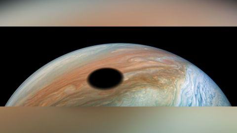 Jupiter's volcanically active moon Io casts its shadow on the planet.