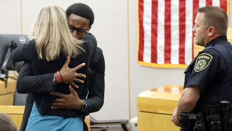 Botham Jean's younger brother Brandt Jean hugs convicted murderer and former Dallas Police Officer Amber Guyger after delivering his impact statement to her after she was sentenced to 10 years in jail, Wednesday, Oct. 2, 2019, in Dallas. Guyger shot and killed Botham Jean, an unarmed 26-year-old neighbor in his own apartment last year. She told police she thought his apartment was her own and that he was an intruder. (Tom Fox/Dallas Morning News via AP, Pool)