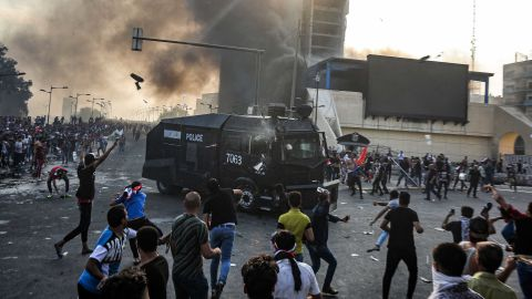 Protesters clash with an Iraqi riot police vehicle during a demonstration against state corruption and poor services, between the capital Baghdad's Tahrir Square and the high-security Green Zone district, on October 1, 2019. - Security forces used water cannons and tear gas to disperse more than 1,000 protesters in central Baghdad. Iraq is considered the 12th most corrupt country in the world according to Transparency International. Power cuts are rampant, water shortages are common and unemployment is high, particularly among youth. (Photo by AHMAD AL-RUBAYE / AFP)        (Photo credit should read AHMAD AL-RUBAYE/AFP/Getty Images)