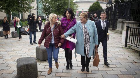 Sarah Ewart (L) alongside her mother Jane Christie (R) and Grainne Teggart (C) of Amnesty International leave Belfast High Court.