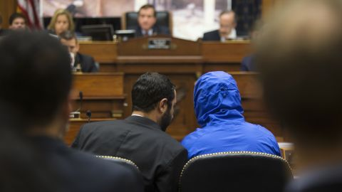 Syrian defector Caesar conceals his identity as he listens with a translator to the House Foreign Affairs Committee in 2014.