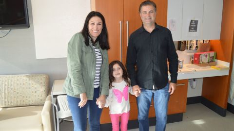 Sophia is seen here, smiling with her parents.