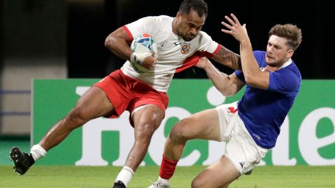 Tonga's Atieli Pakalani, left, is tackled by a French defender at the Kumamoto Stadium.