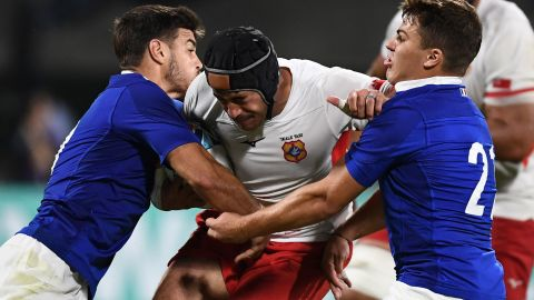 Tonga's centre Mali Hingano (C) is held up by France's  fly-half Romain Ntamack (L) and France's scrum-half Antoine Dupont (R).