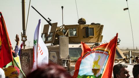 """A soldier sits atop an armoured vehicle during a demonstration by Syrian Kurds against Turkish threats at a US-led international coalition base on the outskirts of Ras al-Ain town in Syria's Hasakeh province near the Turkish border on October 6, 2019. - Ankara had reiterated on October 5 an oft-repeated threat to launch an """"air and ground"""" operation in Syria against a Kurdish militia it deems a terrorist group. (Photo by Delil SOULEIMAN / AFP) (Photo by DELIL SOULEIMAN/AFP via Getty Images)"""