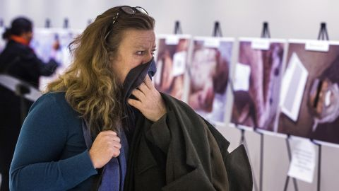 A woman reacts as she looks at a gruesome collection of Caesar's images at the United Nations Headquarters in New York.