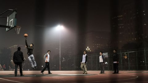BEIJING, CHINA - NOVEMBER 26:  Chinese men play a game of pick-up basketball on an outdoor court in smoggy weather on November 26, 2014 in Beijing, China.United States President Barack Obama and China's president Xi Jinping agreed on a plan to limit carbon emissions by their countries, which are the world's two biggest polluters, at a summit in Beijing earlier this month.  (Photo by Kevin Frayer/Getty Images)