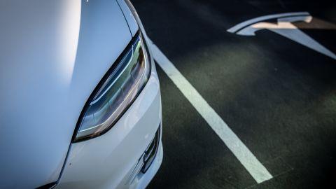 A Tesla logo marks an empty parking bay next to a Model X electric vehicle.