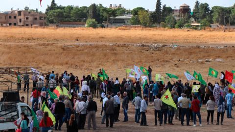 Kurdish people in Ras al-Ain, Syria, wave their group's flags as they protest against a military operation on Monday, October 7.